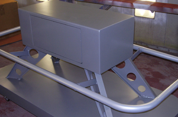 Picture of a gray metal device on wheels.